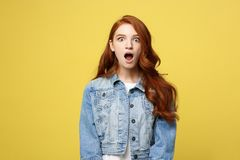 Close up Portrait amaze young beautiful attractive redhair girl shocking with something. Isolated on Bright Yellow. Background. Copy space stock photography