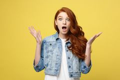 Close up Portrait amaze young beautiful attractive redhair girl shocking with something. Isolated on Bright Yellow stock images
