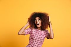 Close-up portrait of amazed african woman in dress touching her. Afro hairstyle, looking upward, isolated on yellow background Royalty Free Stock Photo