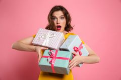 Close-up portrait of amazed beautiful woman holding bunch of pre. Sents, looking at camera, isolated on pink background Stock Image