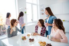 Close up portrait amazing beautiful she her ladies family meeting sister cousins nephews stand sit round big white table. Bright kitchen hold cups share novelty stock photography