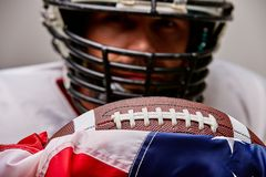 Close up portrait of american Football Player in helmet with ball and american flag proud of his country, on a white stock image