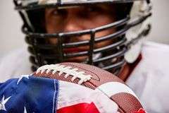 Close up portrait of american Football Player in helmet with ball and american flag proud of his country, on a white stock photography