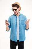 Close-up portrait of angry man shouting at his smartphone. Close-up portrait of angry young man shouting at his smart phone isolated on white background Stock Photos