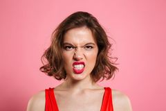 Close-up portrait of angry young woman with red lips looking at Stock Photo