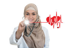 Close up portrait of arab female doctor smiling while using stethoscope stock photography