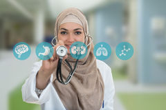 Close up portrait of arab female doctor smiling while using stethoscope stock photos