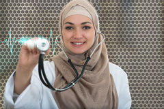 Close up portrait of arab female doctor smiling while using stethoscope Stock Images