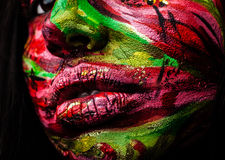 Close-up portrait of an artistic woman painted with red & green color. Royalty Free Stock Photos