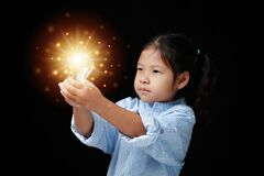 Close-up portrait Asian kid girl highly confident, a committed face with two hands holding a lamp orange light.