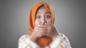 Muslim Lady Shocked and Closing her Mouth. Close up portrait of Asian muslim woman wearing hijab closing her mouth with fingers. Worried gesture, can& x27;t say stock photo