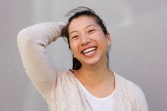 Close up portrait of asian woman smiling with hand in hair Royalty Free Stock Images