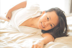 Close up portrait of Asian woman on white shirt  lay down on whi Royalty Free Stock Image