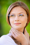 Close-up portrait of attractive. Close-up portrait of young beautiful woman wearing eyeglasses looking somewhere at summer green park Royalty Free Stock Images