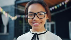 Close-up portrait of attractive African American teenager in glasses smiling stock video footage