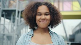 Close-up portrait of attractive African American teenager smiling outdoors stock footage