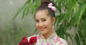 Attractive asian woman in traditional costume with a bouquet of flowers of red roses looking to camera and smiling on stock video footage