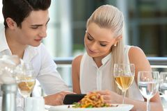 Cute couple looking at smart phone at dinner. Royalty Free Stock Photo