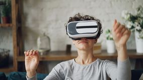 Close-up portrait of attractive curly-haired girl putting on augmented reality glasses and moving head and hands. Close-up portrait of attractive curly-haired stock video footage