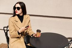 Close up portrait of attractive elegant woman sitting alone with cup of strong coffee and her mobile phone, watching what is stock photo