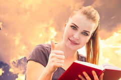 Close-up portrait of attractive girl reading and showing thumbup Royalty Free Stock Images