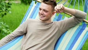 Close-up portrait of a happy man lies on a hammock in the garden, smiles and relaxes stock video footage