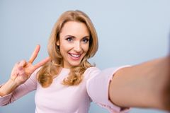 Close up portrait of attractive mature carefree joyful woman wit. H blonde curly hairdo, she is taking a selfie and demonstrating two fingers, isolated on grey royalty free stock photo