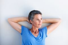 Close up attractive mature woman staring in contemplation. Close up portrait of attractive mature woman staring in contemplation with hands behind head royalty free stock images