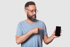 Close up portrait of attractive middle aged male in gray casual t shirt, stands against white wall, pointing with fore finger on. Blank screen of his smartphone stock photos