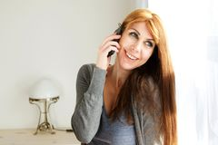 Attractive mature woman talking on phone. Close up portrait of attractive middle aged woman standing at home and talking in cell phone Royalty Free Stock Image