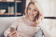 Close up portrait of attractive pretty woman  siting on couch in. Living room, having, using earphones, holding smart phone, listening music, looking at screen Royalty Free Stock Image