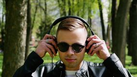Close-up portrait of attractive student, man puts on headphones listening to music stock video