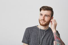 Close up portrait of attractive tattooed european man with beard and fashionable hairstyle plugging ear with earphone Royalty Free Stock Images
