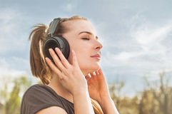 Close up portrait of attractive woman enjoying music on headphon Royalty Free Stock Photos