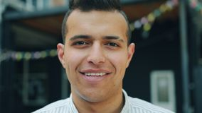 Close-up portrait of attractive young Arab smiling looking at camera outdoors. Standing in city street alone. Positive emotions, beautiful people and urban stock footage