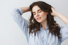 Close up portrait of attractive young brunette student girl with closed eyes,holding hands in hair with calm and sexy. Vibes Royalty Free Stock Image