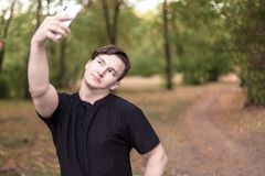 Young caucasian man gets selfie on mobile phone in the park stock images
