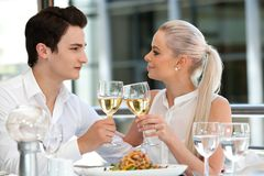 Attractive couple making a toast at dinner. Stock Image