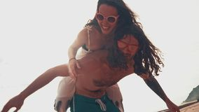 Close up portrait of a attractive young and energetic couple having fun on the beach. Woman piggyback riding a man and. Laughing. Traveling and Vacation concept stock video