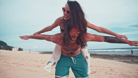 Close up portrait of a attractive young and energetic couple having fun on the beach. Woman piggyback riding a man and. Laughing. Traveling and Vacation concept stock footage