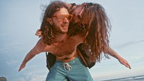 Close up portrait of a attractive young and energetic couple having fun on the beach. Woman piggyback riding a man and. Laughing. Traveling and Vacation concept stock video footage