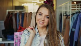 Close-up portrait of attractive young girl standing with paper bags in clothing shop and looking at camera smiling. Close-up portrait of attractive young girl stock video footage
