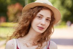 Close up portrait of attractive young lady in straw hat. Foxy haired charming woman with brown eyes looking at camera with gentle stock photography