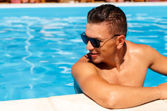 Close up portrait of attractive young man  in sunglasses resting. On edge of swimming pool Royalty Free Stock Image