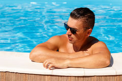 Close up portrait of attractive young man  in sunglasses resting. On edge of swimming pool Stock Photography