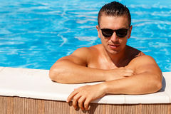 Close up portrait of attractive young man  in sunglasses resting. On edge of swimming pool Stock Image