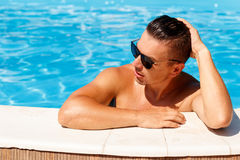 Close up portrait of attractive young man  in sunglasses resting. On edge of swimming pool Royalty Free Stock Photography
