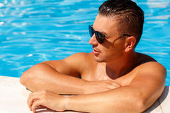 Close up portrait of attractive young man  in sunglasses resting. On edge of swimming pool Royalty Free Stock Photo