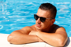 Close up portrait of attractive young man  in sunglasses resting. On edge of swimming pool Royalty Free Stock Photos