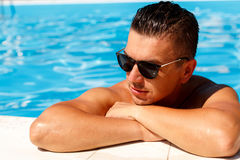 Close up portrait of attractive young man  in sunglasses resting. On edge of swimming pool Stock Photos